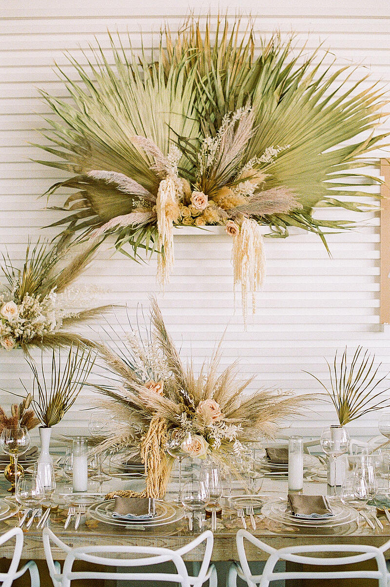 Hanging installation and tablescape by With Love Floral Co at borrowed BLU event featuring Mayesh products including dried pampas grass, bleached preserved ruscus and amaranthus, roses.