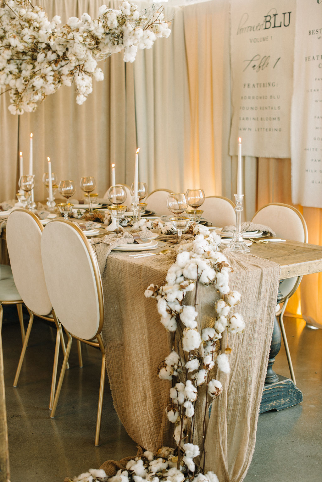 Hanging installation and tablescape by Crowned Events at borrowed BLU event using cotton on a stick from Mayesh Wholesale.