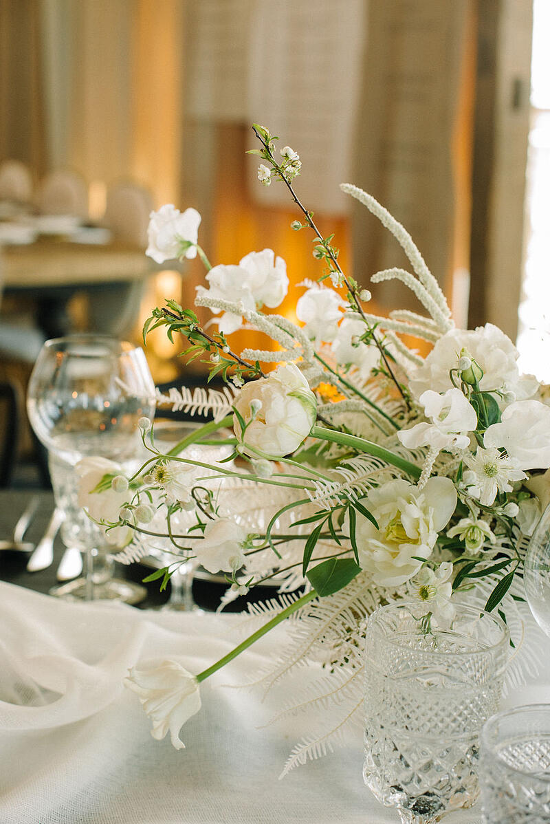 Centerpiece featuring white tulips, white sweet peas, bleached preserved fern from Mayesh Wholesale.