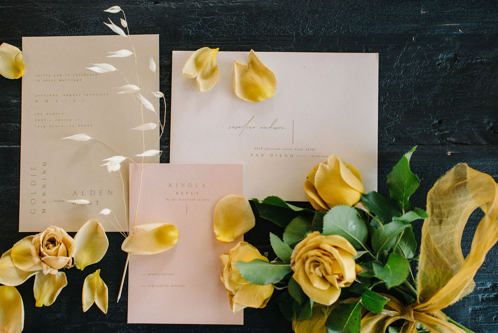 Invitation flat lay including yellow roses from Mayesh Wholesale.