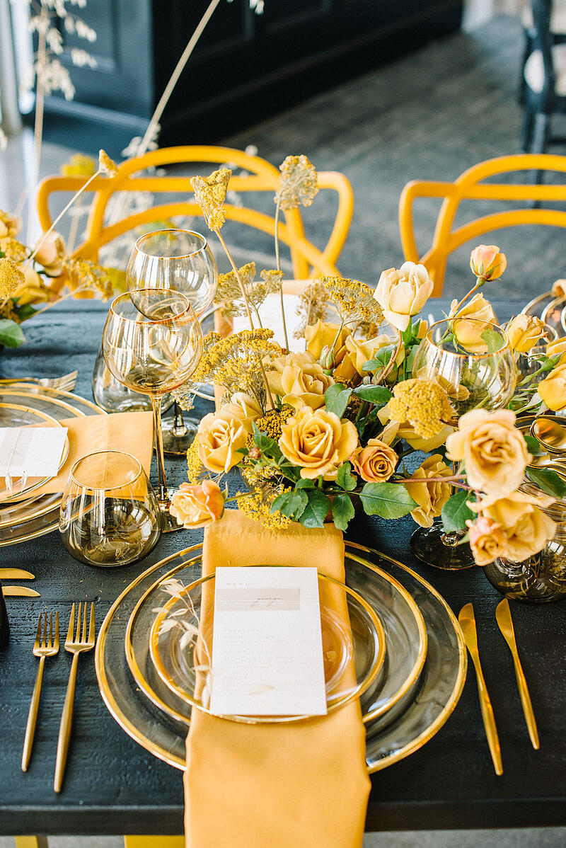 Centerpieces with yellow yarrow and yellow roses from Mayesh Wholesale.