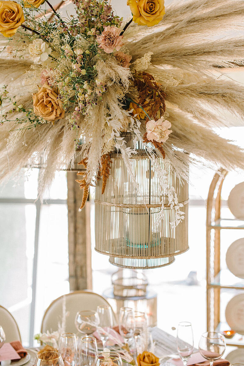Hanging installation featuring pampas grass, yellow roses, toffee roses, lisianthus, bleached preserved ruscus and carnations from Mayesh Wholesale.