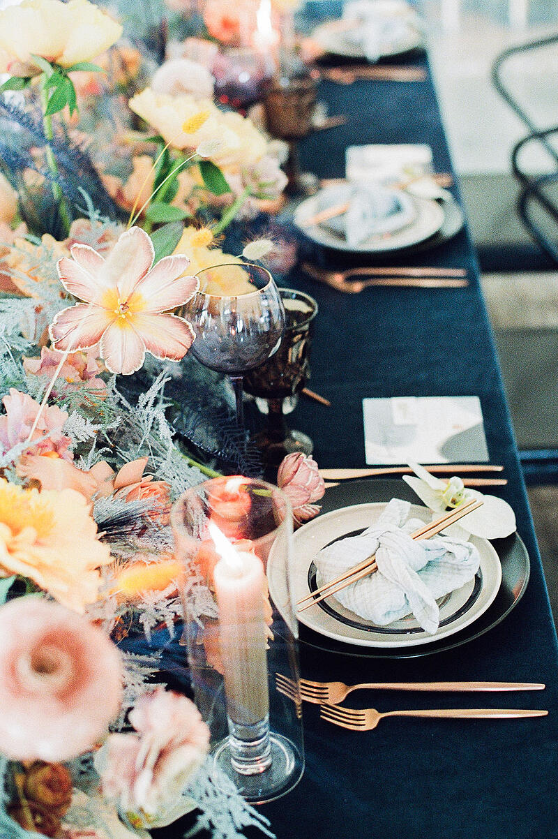 Tablescape featuring dyed brownie tulips, plumosus, ranunculus, roses, peonies from Mayesh Wholesale.