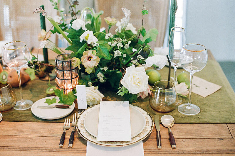 Tablescape featuring roses, icelandic poppies, white roses, white astrantia, tulips from Mayesh Wholesale.