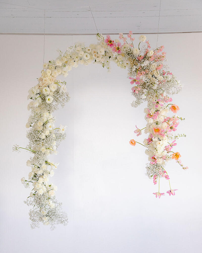blush, pink, peach, and white hanging floral arch installation