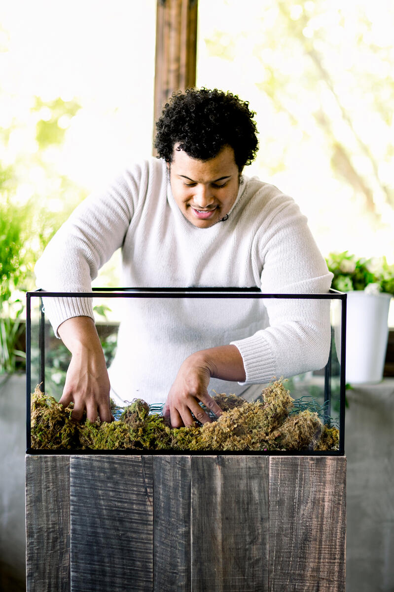 Shean Strong designing floral terrarium with a sheet moss base