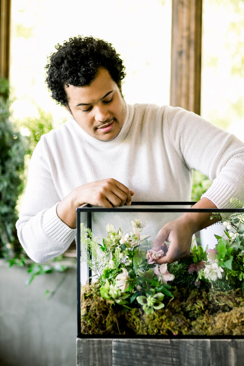 Shean Strong designing floral terrarium with helleborus, pennycress, white snow berry and sheet moss