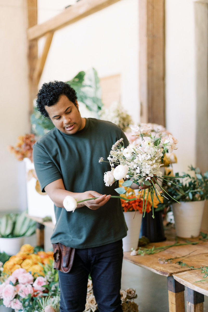 Shean Strong designing a bouquet with ranunculus, roses and hydrangea at the Mayesh Design Star workshop in Austin TX