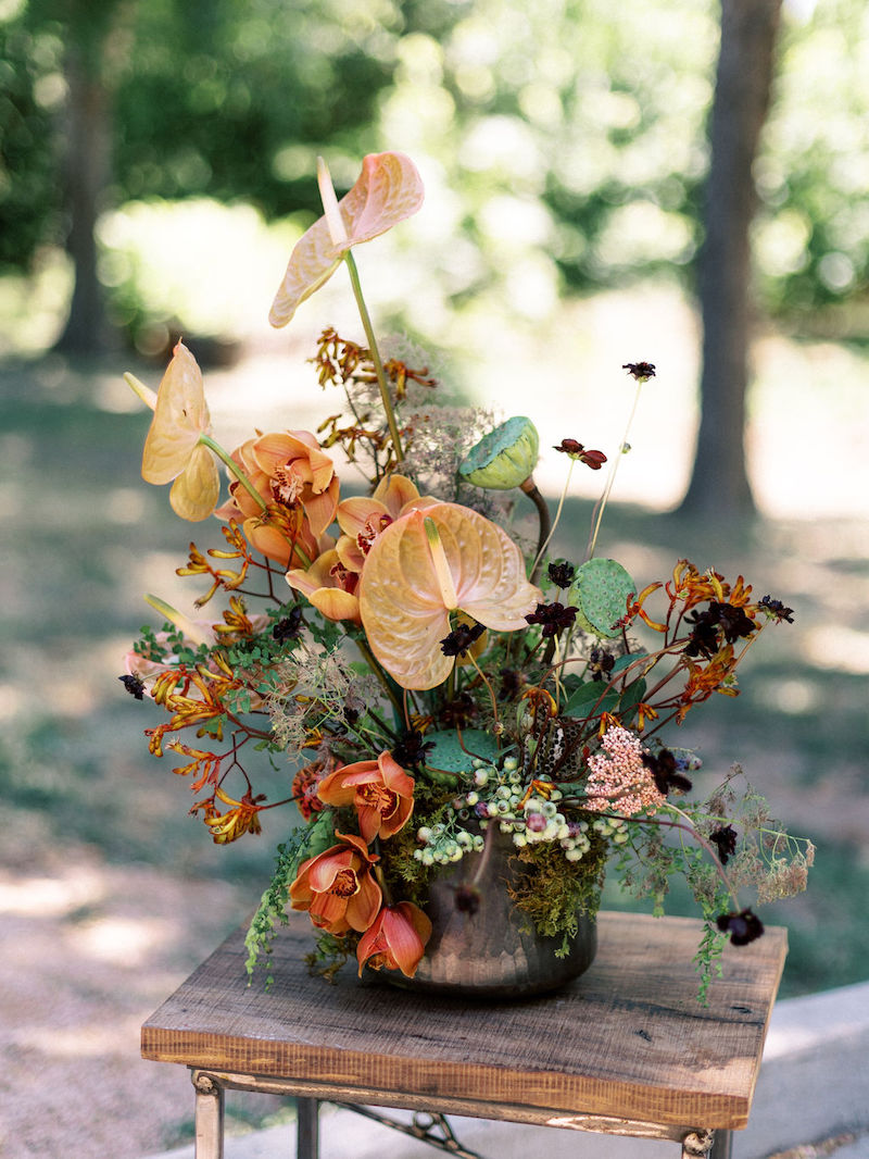Floral arrangement featuring kangaroo paw, chocolate cosmos, pink anthurium, cymbidiums, maidenhair fern, moss, lotus pods