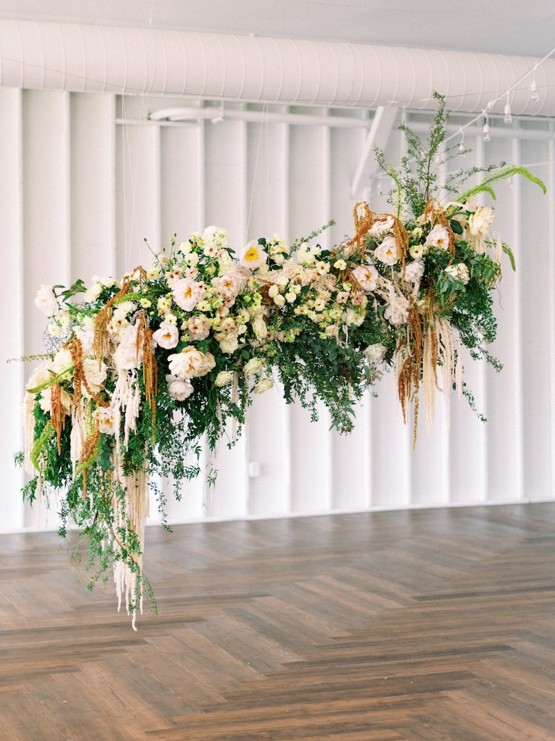 hanging floral installation featuring hanging amaranthus, garden roses, spirea, butterfly ranunculus
