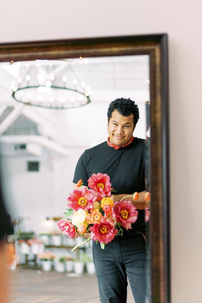 Shean Strong designing a bouquet with garden roses, tree peonies and ranunculus