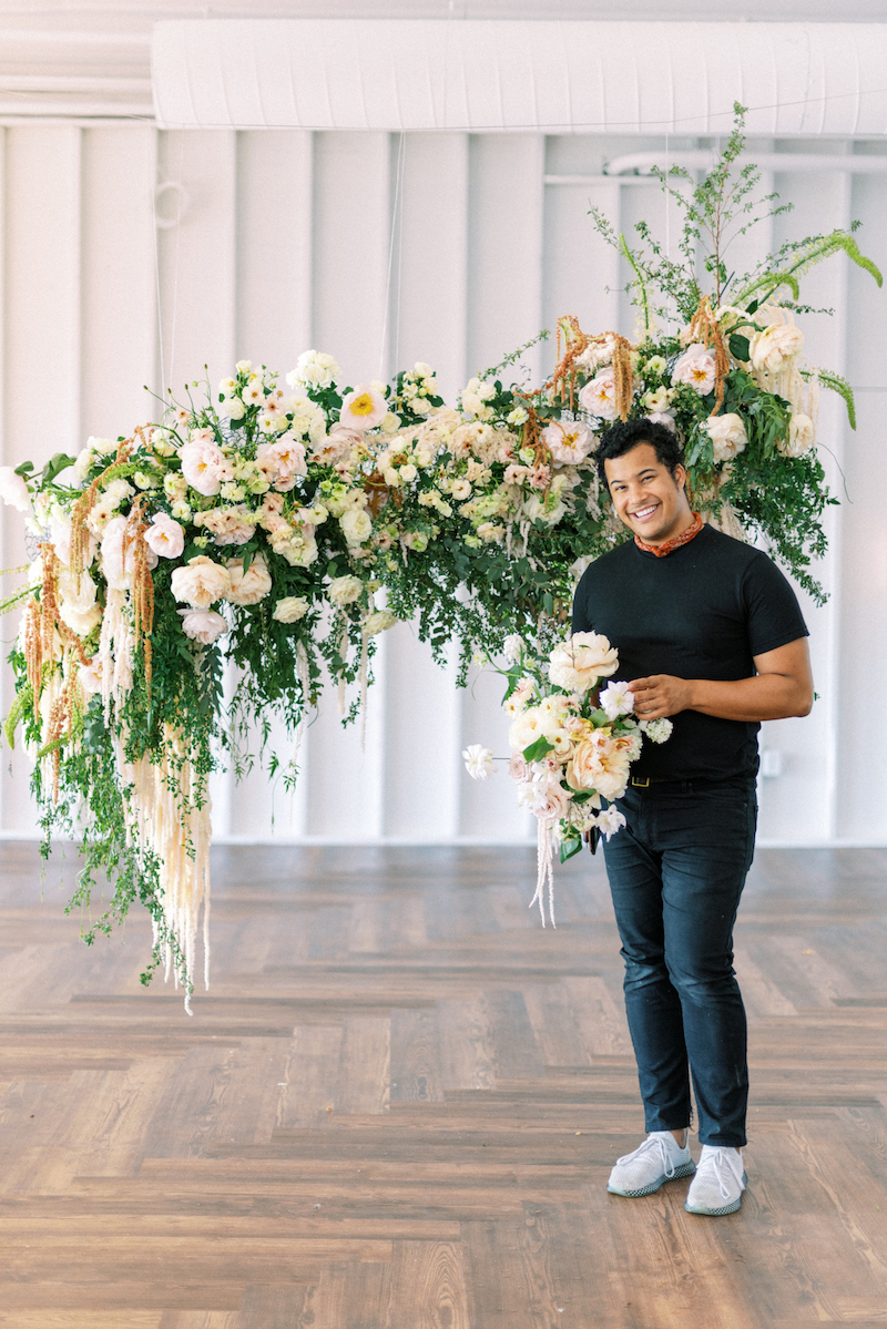 Shean Strong with hanging floral installation and bouquet featuring hanging amaranthus, garden roses, spirea, butterfly ranunculus