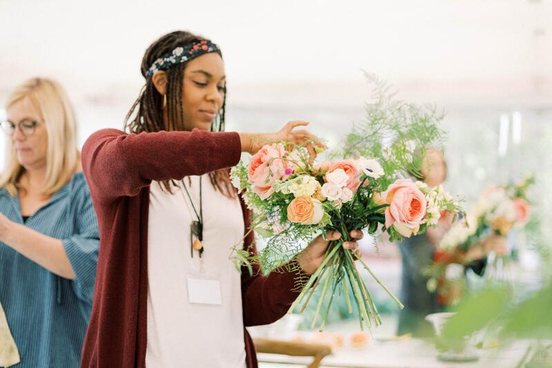 Attendee making bouquet with roses, plumosus, spray roses, anemones at the Holly Chapple teaches at Mayesh International Workshop in Quito, Ecuador.